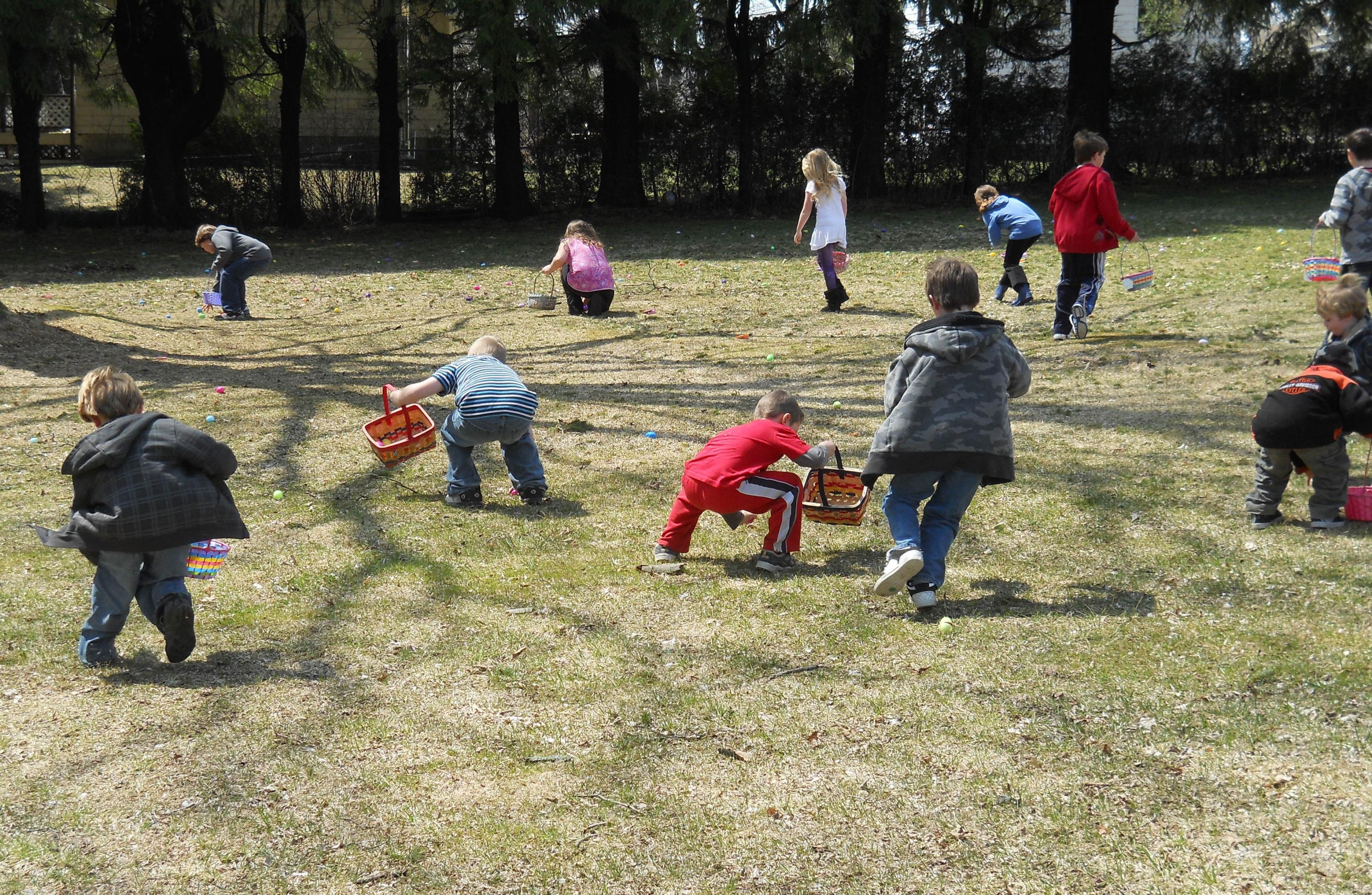 several small children in a park picking up easter eggs in the grass
