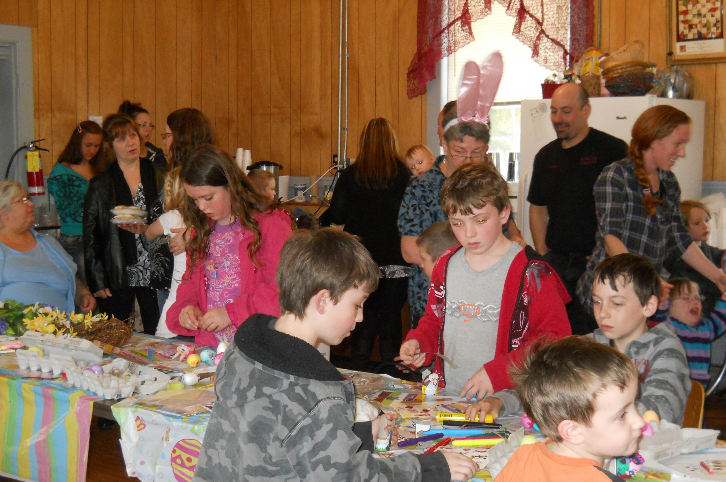 several children and adults painting easter eggs and making crafts