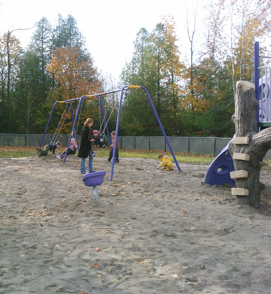 Kids playing on swings with parent