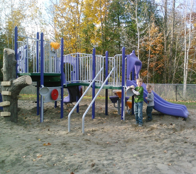 kids playing in a playground on a nice fall day