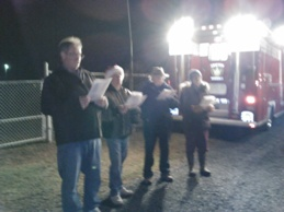 People singing carols lit up by firetruck